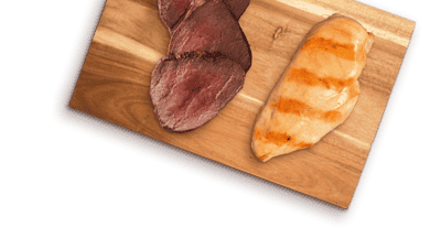 slices of beef and chicken breast on a wooden board