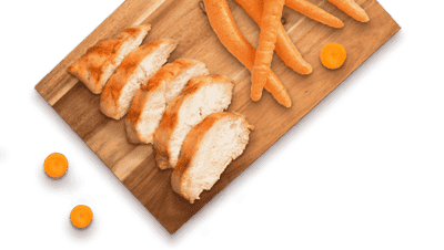 slices of chicken and carrots on a wooden board