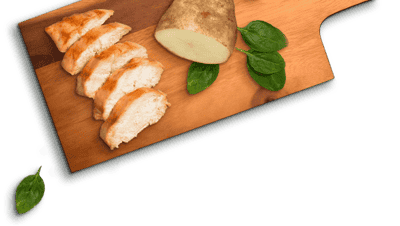 slices of chicken, potato, and spinach leaves on a wooden board