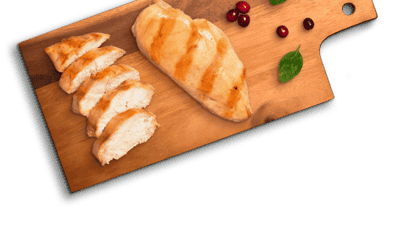 slices of chicken next to one grilled chicken breast, next to cranberries and spinach on a wooden cutting board