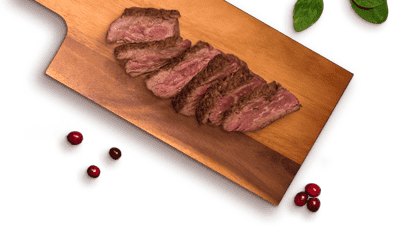 beef slices on a cutton board, and spinach and cranberries