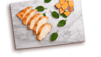 chicken slices, spinach leaves, sweet potato chunks on marble cutting board