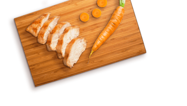slices of grilled chicken and carrot with slices on cutting board