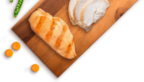carrots, peas, grilled chicken breast, and slices of chicken on a wooden board