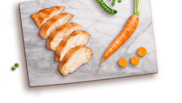 chicken slices, carrot, peas on marble board