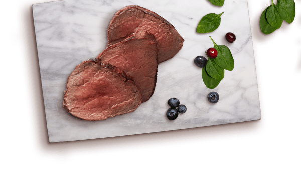 bison slices, blueberries, cranberries, spinach on marble board