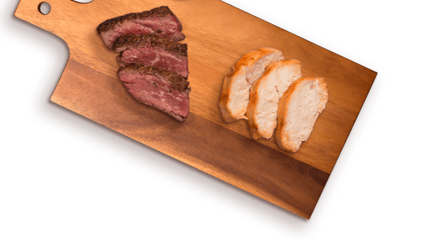 slices of beef and grilled chicken on cutting board