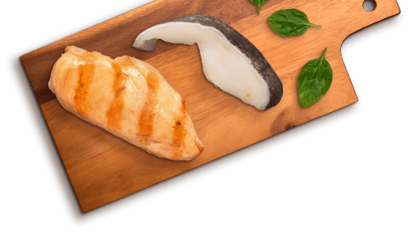 grilled chicken and slice of ocean whitefish and spinach leaves on cutting board