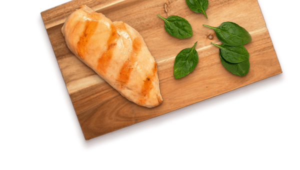 grilled chicken breast and spinach leaves on a wooden board