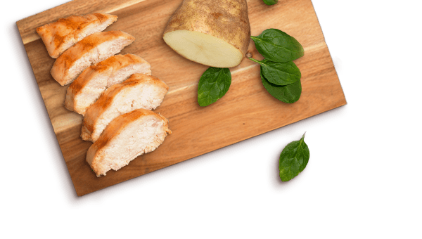 Freshpet Select slices of chicken, potato, spinach on a wooden board