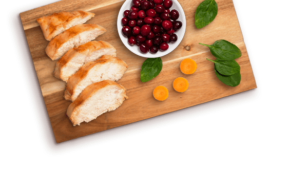 sliced grilled chicken, cranberries in a bowl, carrot slices, leaves of spinach on a wooden cutting board
