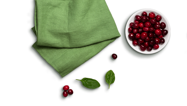 bowl of cranberries, spinach leaves, and a green cloth napkin
