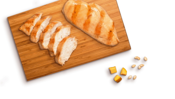 grilled chicken pieces on cutting board with pumpkin pieces