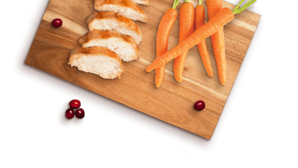 slices of chicken, cranberries, and whole carrots on a wooden board
