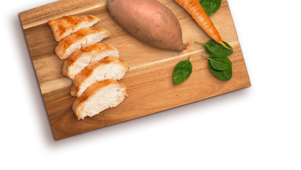 chicken slices, sweet potato, carrot. and spinach leaves on wood cutting board