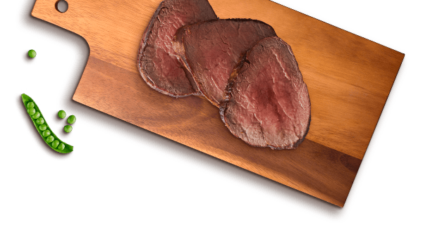 peas and beef slices on wooden cutting board