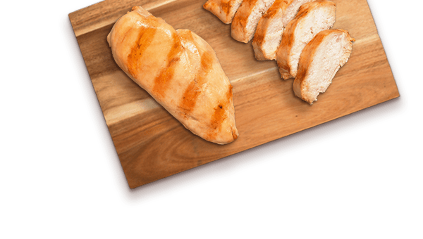 grilled chicken pieces on wooden cutting board
