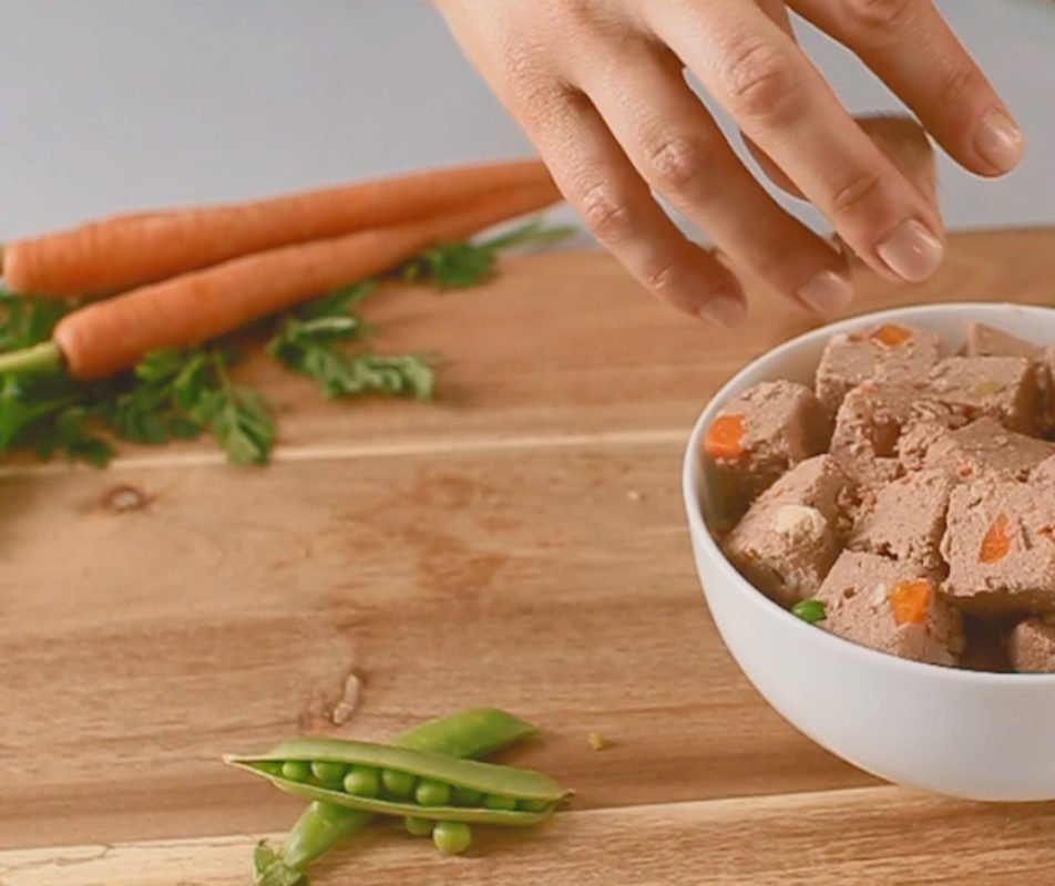 whole carrots, peas, and freshpet in a bowl with a hand reaching for the freshpet food in the bowl