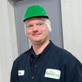 worker in freshpet blue jacket with safety glasses and green safety hat on