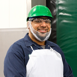 worker in blue polo and white apron with safety glasses and green safety hat on