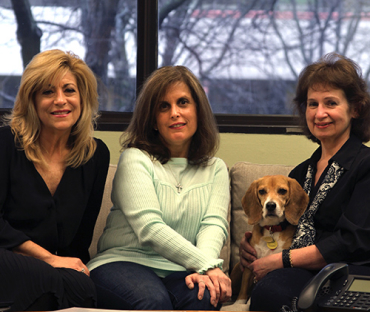 three women sitting on a couch posing for a photo with small dog sitting in between two of the women